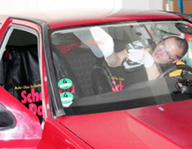 Eine neue Frontscheibe wird im Auto verbaut.